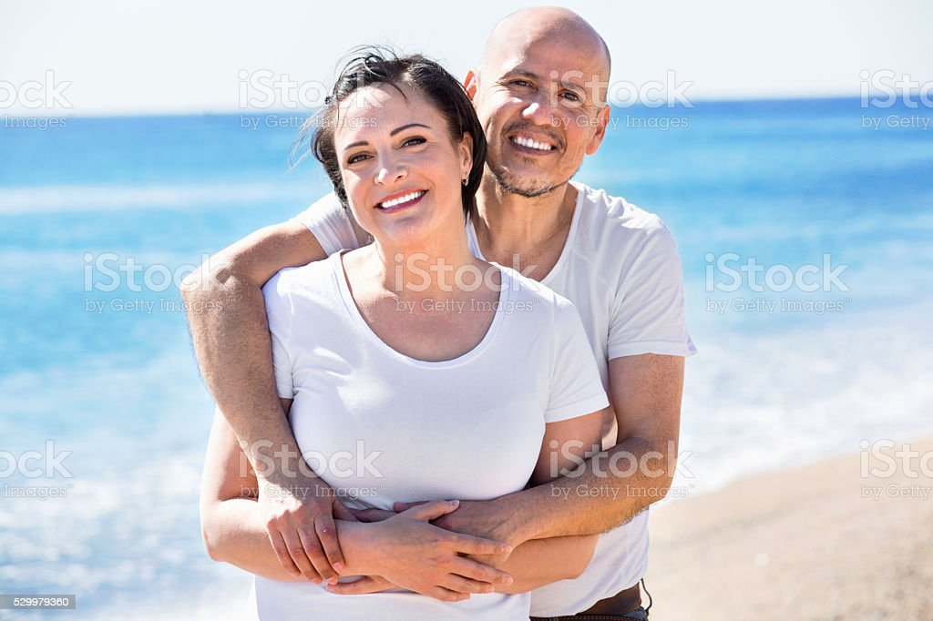 Couple gladly hugging each other and enjoying the beach stock photo