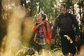 Loving couple going for a camping trip. Man and woman backpackers walking through forest holding hands and looking away.