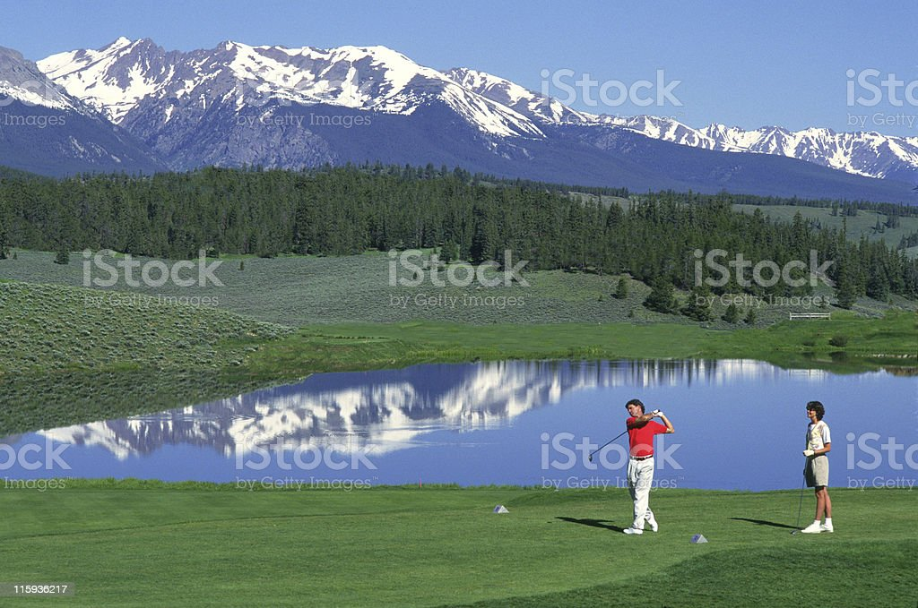 Couple Golfing with Lake and Mountains royalty-free stock photo