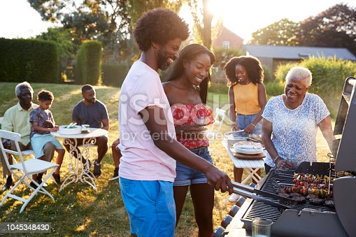 istock Couple grilling at a black multi generation family barbecue 1045348430