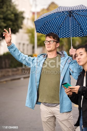 Shot of a couple standing outdoors under umbrella and hailing for taxi