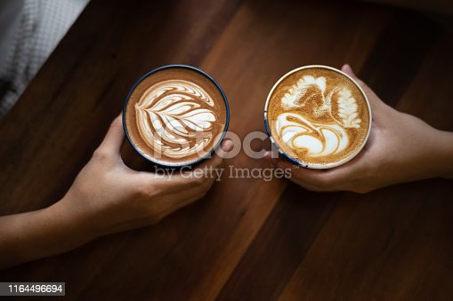 istock Couple hands holding two cups of coffee lattes with coffee art on top of wooden table 1164496694