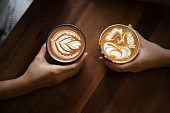 Couple hands holding two cups of coffee lattes with coffee art on top of wooden table