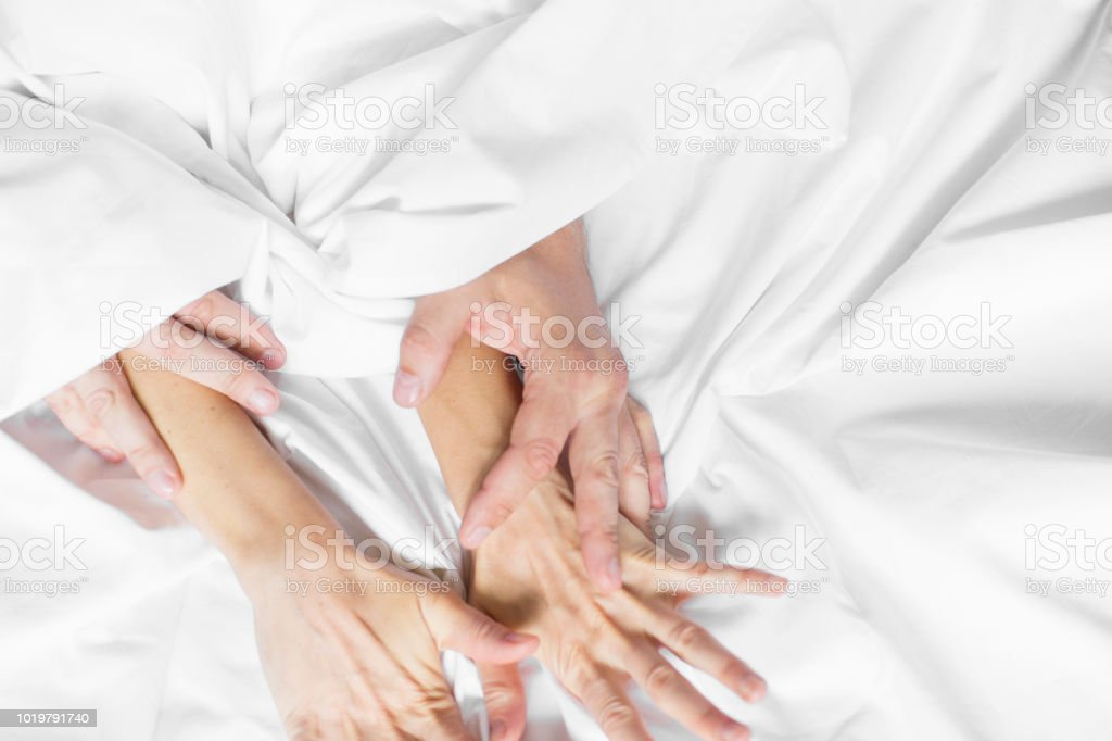 couple hands pulling white sheets in ecstasy, orgasm. Concept of passion.  Oorgasm.