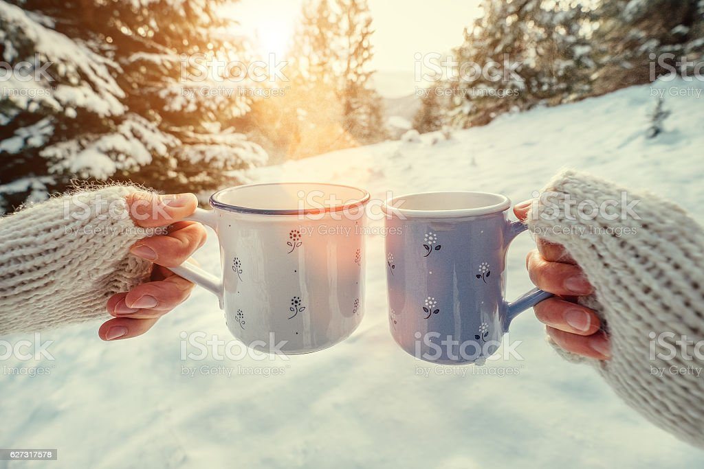 Couple hands with mugs with hot tea in winter forest stock photo