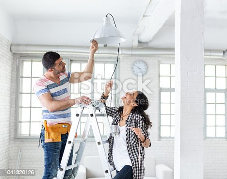 Couple hanging a lamp in new apartment