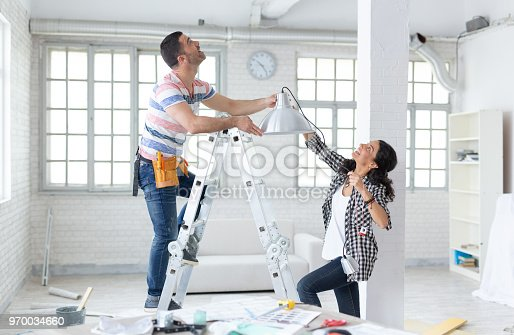Couple hanging a lamp in new home, man on ladder.Property Services. New Home.
