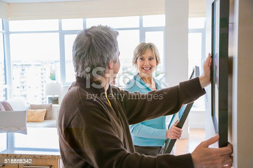 istock Couple hanging art in house 518888342
