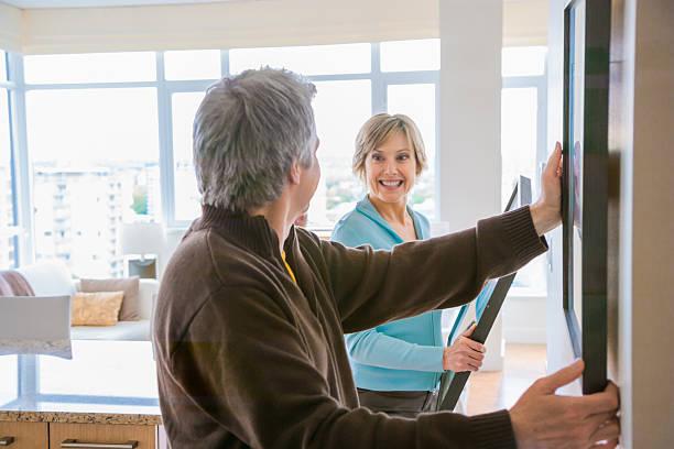 couple hanging art in house - happy weekend bilder stock-fotos und bilder