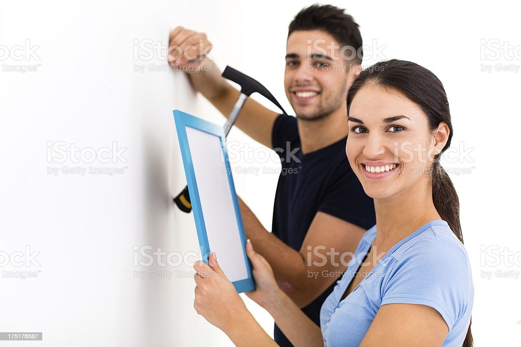 Couple hanging picture frame on wall stock photo