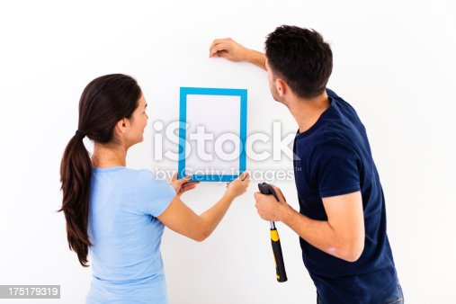istock Couple hanging picture frame on wall 175179319