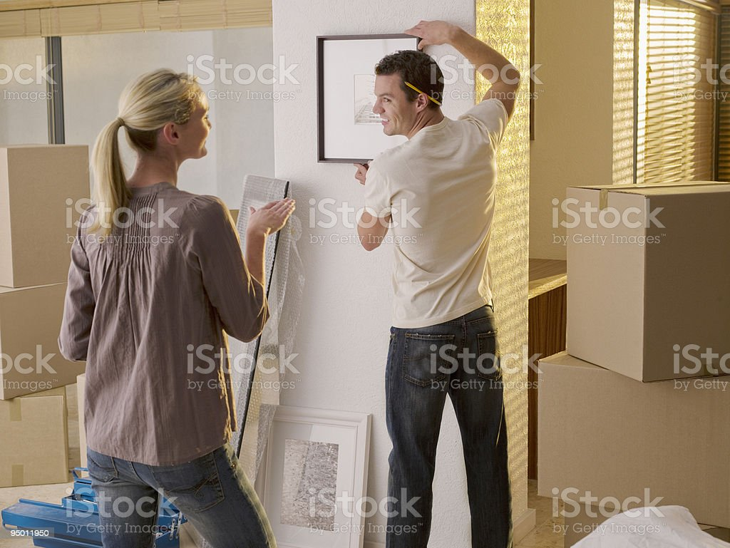 Couple hanging picture in new house stock photo