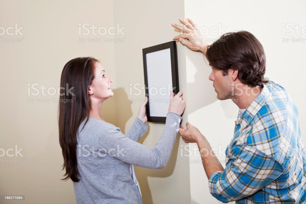 Couple hanging picture on wall stock photo