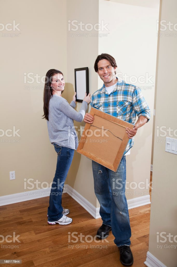 Couple hanging pictures on wall stock photo
