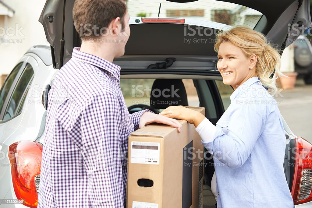 Couple happily unloading new television from car trunk stock photo