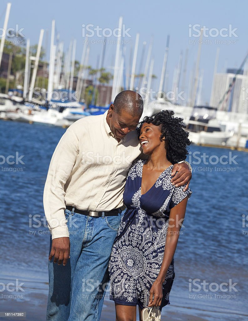 A couple happily walking on the beach stock photo