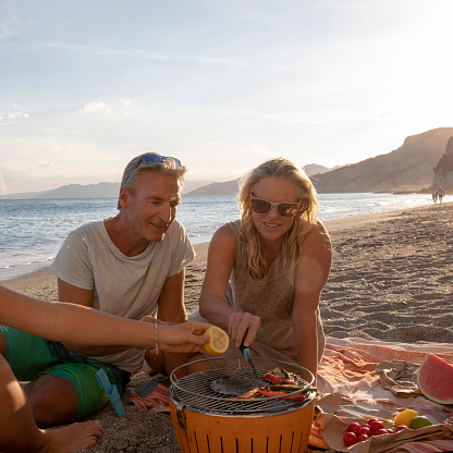 Couple have a barbecue on the beach at sunset
