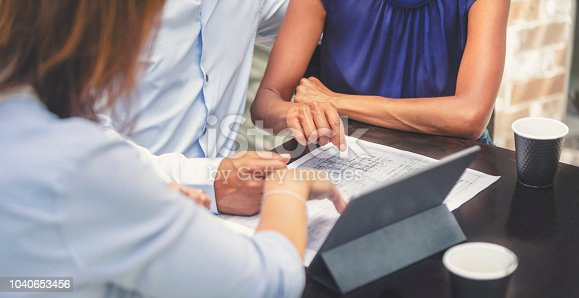 istock Couple having a business meeting with a architect or real estate agent. 1040653456