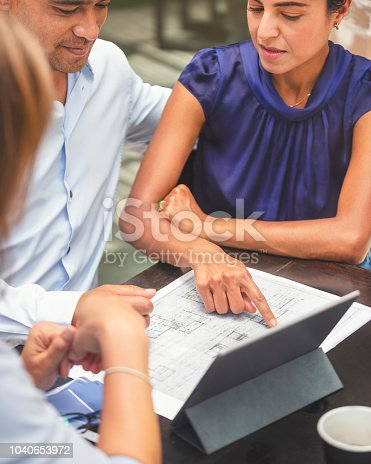 istock Couple having a business meeting with a architect or real estate agent. 1040653972
