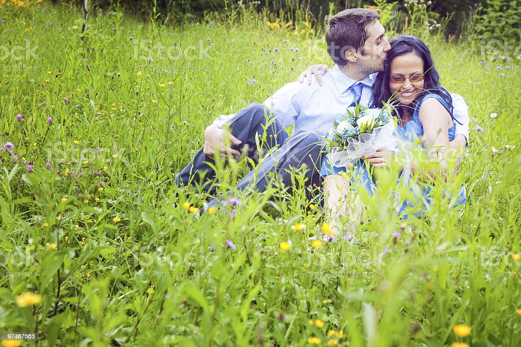 Couple having a candid romantic kiss in the grass royalty-free stock photo