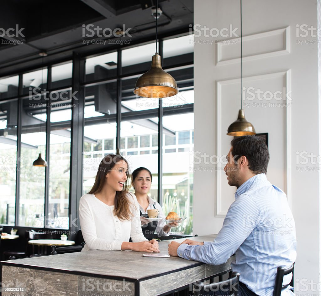 Couple having a cup of coffee at a cafe stock photo