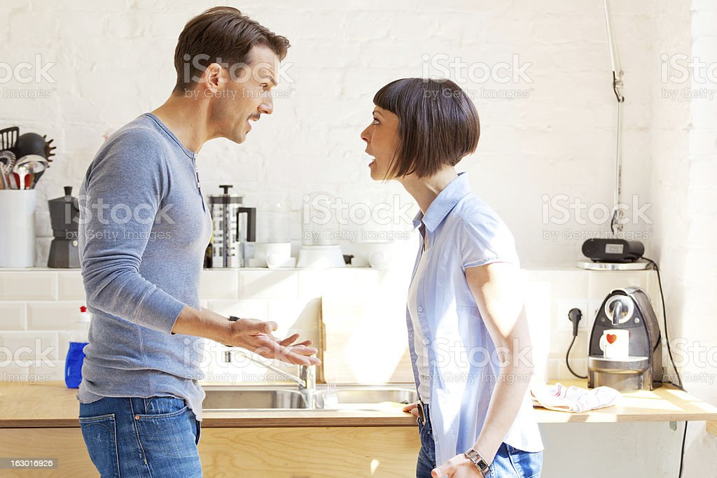 Couple having a discussion in the kitchen stock photo