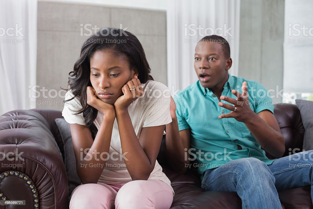 Couple having a dispute on the sofa stock photo