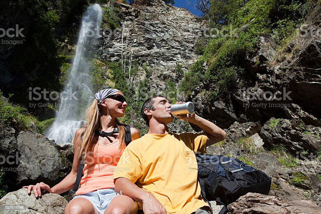 Couple having a drink by waterfall stock photo