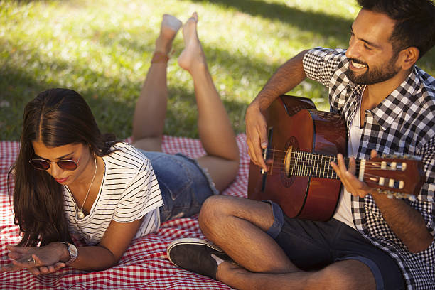 Couple having a good time Young couple in public park enjoying their time together while the male plays guitar serenading stock pictures, royalty-free photos & images