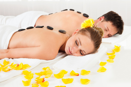 Couple having a hot stone massage treatment in a spa relaxing as the heat from the stones relaxes their muscles