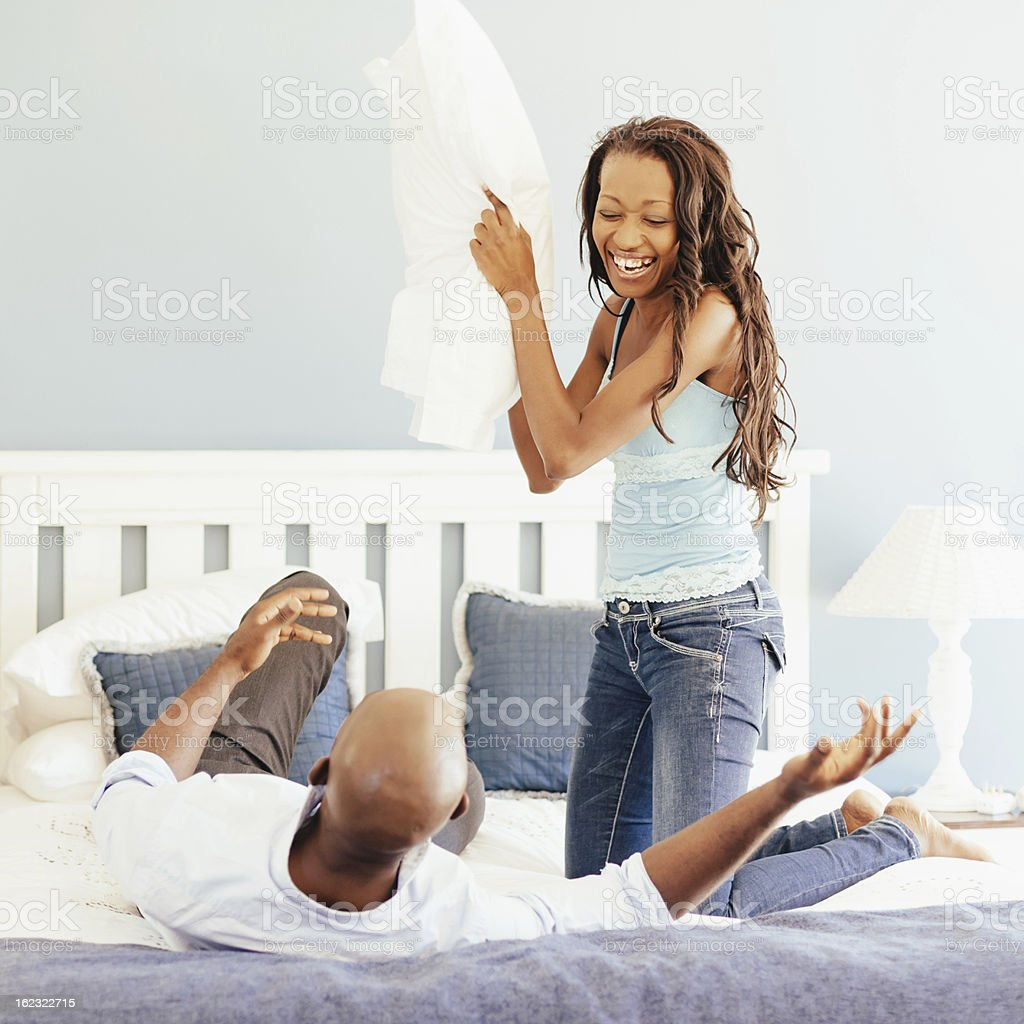 Couple Having a Pillow Fight in Bedroom Happy couple having fun in their bedroom. Joking, laughing in a pillow fight. Man lying on his back, his wife holding a large pillow ready to throw it towards him. 20-29 Years Stock Photo
