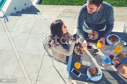 Couple having a romantic breakfast. They are sitting outdoors on the patio. They are having a healthy breakfast with coffee, muesli and toast. There are mobile phones on the table. High angle view with copy space.