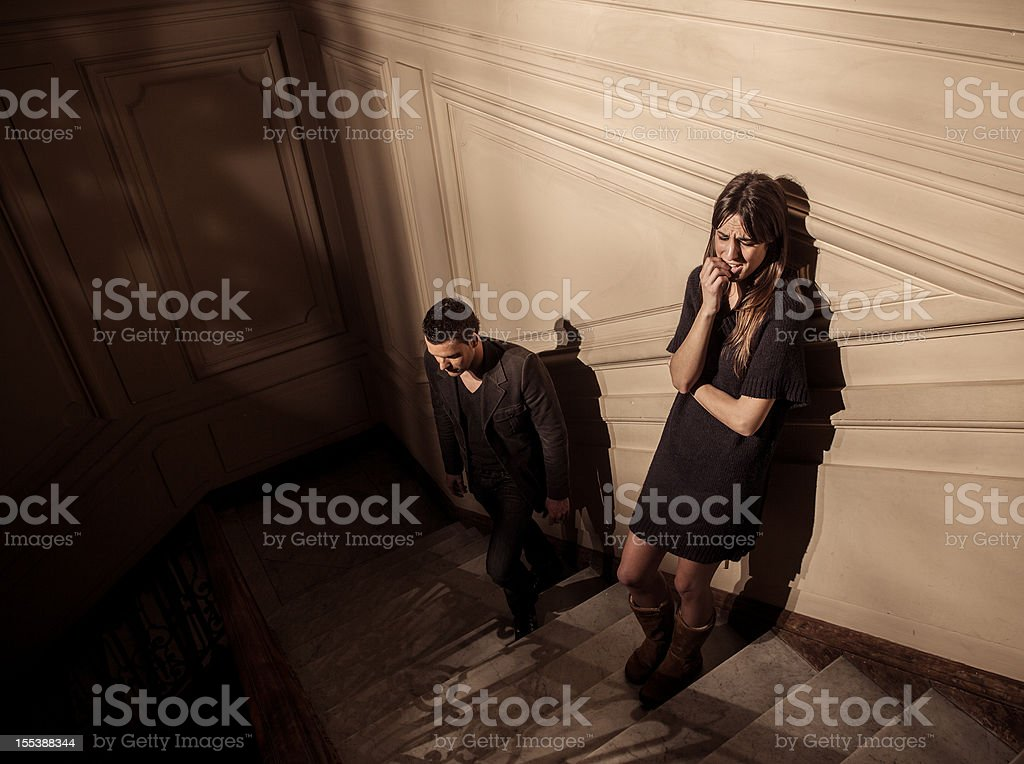 couple having an argument in a dark staircase stock photo