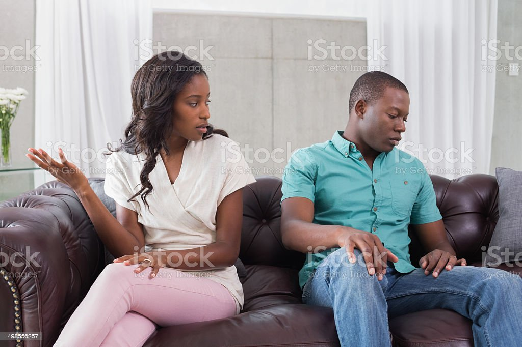 Couple having an argument on the couch stock photo