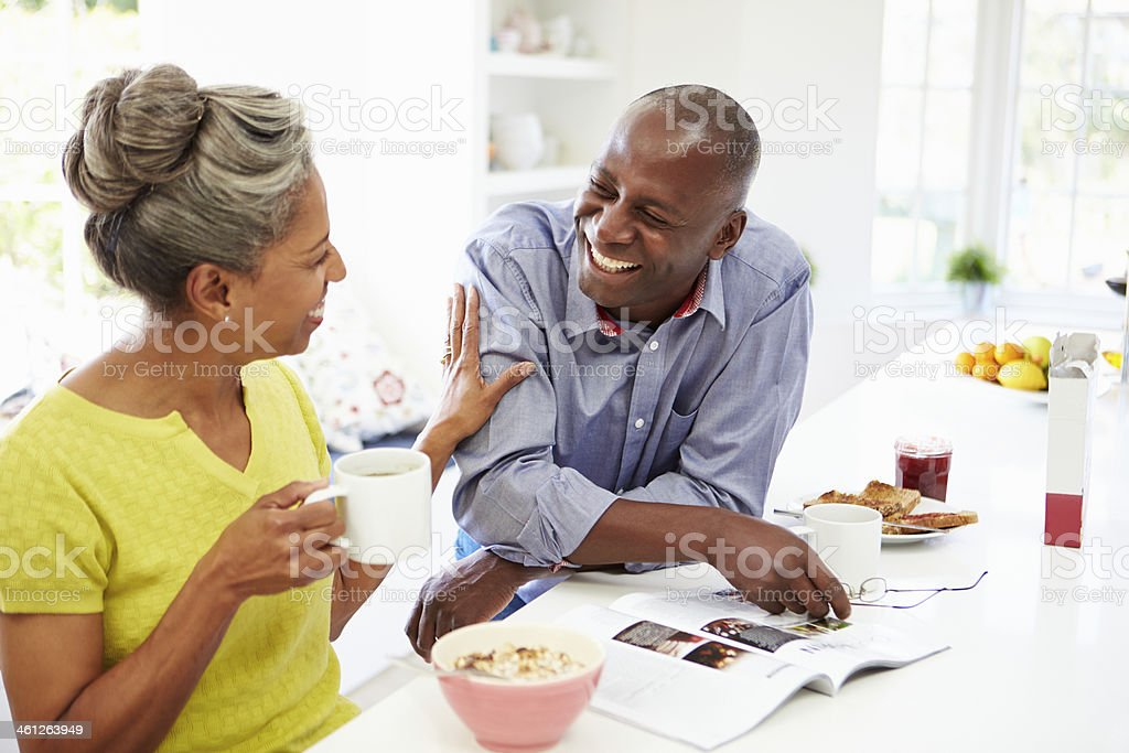 Couple Having Breakfast And Reading Magazine In Kitchen stock photo