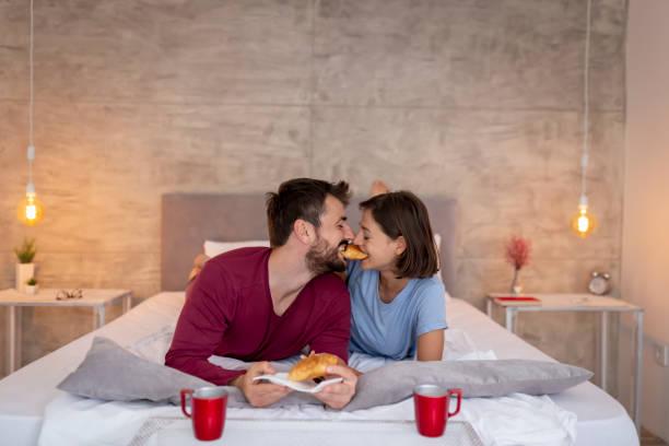 pareja desayunando en la cama - happy couple sharing a cup of coffee fotografías e imágenes de stock