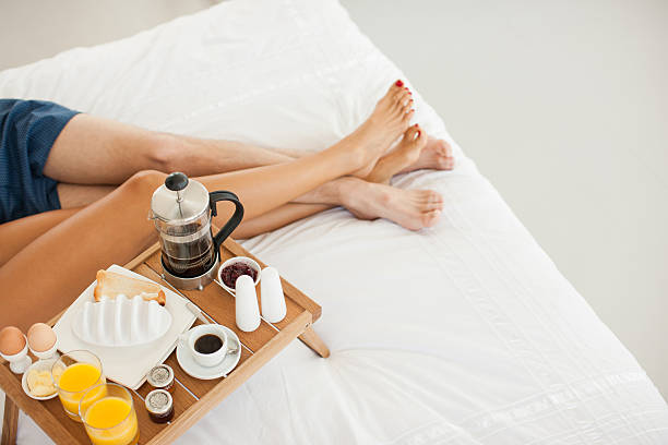 Couple having breakfast in bed stock photo