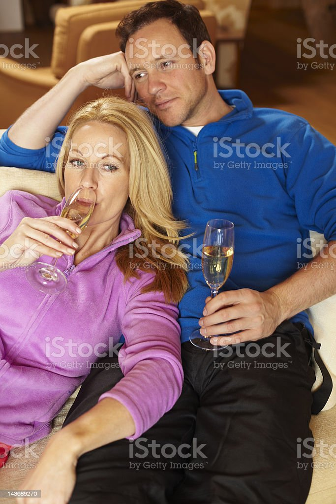 Couple having champagne on sofa royalty-free stock photo