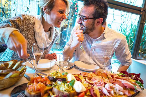 paar mit weihnachts-dinner in einem restaurant - italienischer weihnachten stock-fotos und bilder
