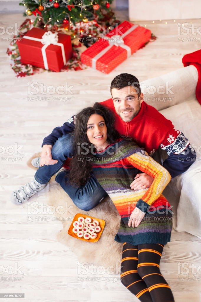 Couple sitting on ground and resting, having fun on Christmas. Both...