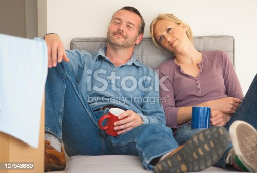 istock Couple having coffee on sofa together 127543680