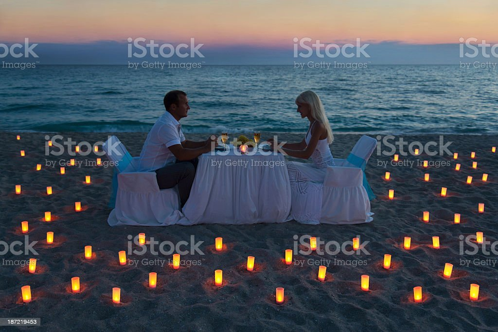 Couple having dinner at beach surrounded by candles royalty-free stock photo