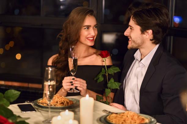 レストランで夕食を持っているカップル - 談笑する ストックフォトと画像