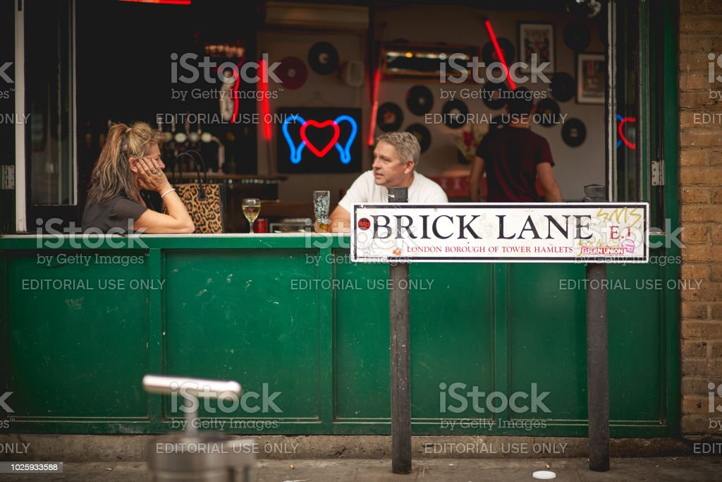 A couple having drinks in a bar in Brick Lane (London). stock photo