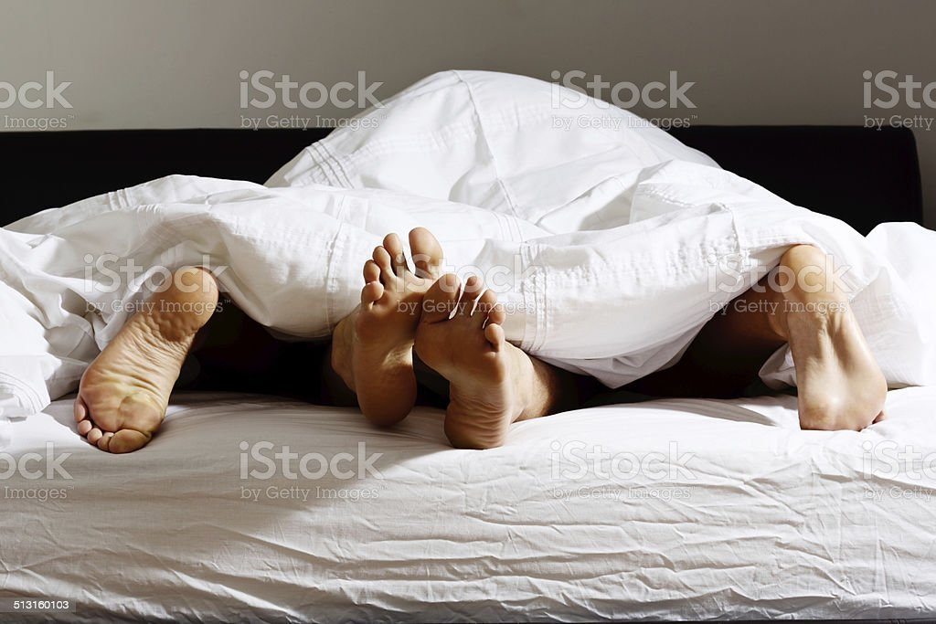 The feet of an anonymous couple having sex under a white duvet.
