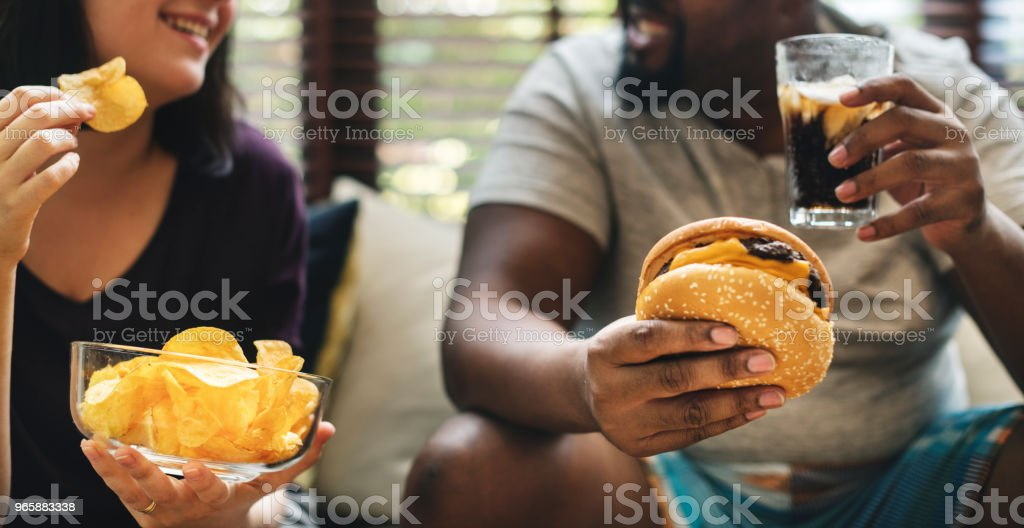 Couple having fast food on the couch - Royalty-free African Ethnicity Stock Photo