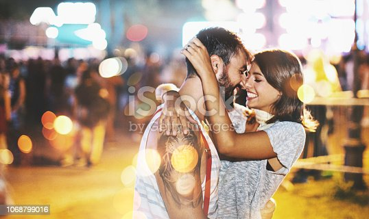 Hugged young couple looking each about to kiss at music festival.