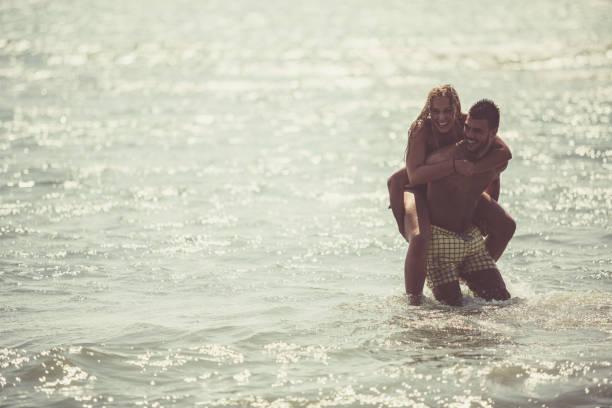 Couple having fun at the beach stock photo