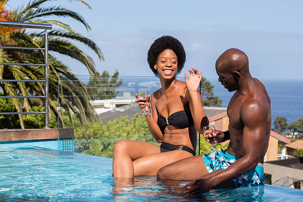 couple having fun by pool - carolinemaryan stock pictures, royalty-free photos & images