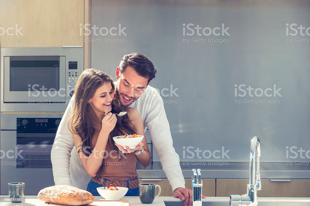 Couple having fun eating breakfast. stock photo